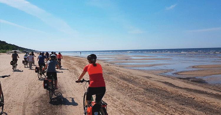 Cyklister på stranden i Letland