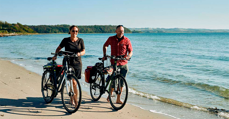 Par trækker cyklerne langs stranden